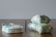 New and used baby diapers on the wooden table background. Three diapers royalty free stock photo