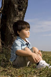 New Vision. Young Asian boy day dreaming by a tree stock photo