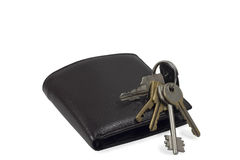 New wallet and old keys. Bunch of keys on closed leather wallet Stock Photos