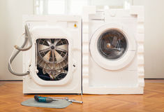 New washing machine and an old defective Royalty Free Stock Photography