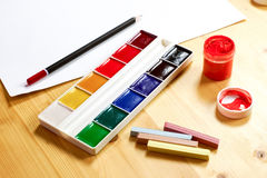 New watercolor crayons and a jar of gouache are standing next to Royalty Free Stock Image