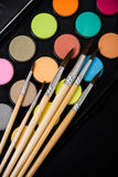 New watercolor paint set and brushes on artist's work desk. Creative art tools on black background closeup stock photos