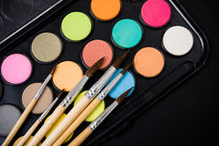 New watercolor paint set and brushes on artist's work desk. Creative art tools on black background closeup royalty free stock photos