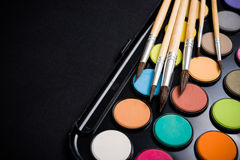 New watercolor paint set and brushes on artist's work desk. Creative art tools on black background closeup stock photo