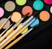 New watercolor paint set and brushes on artist's work desk. Creative art tools on black background closeup royalty free stock images