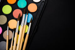 New watercolor paint set and brushes on artist's work desk. Creative art tools on black background closeup royalty free stock photo