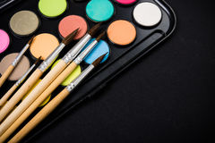 New watercolor paint set and brushes on artist's work desk. Creative art tools on black background closeup stock images