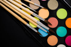 New watercolor paint set and brushes on artist's work desk. Creative art tools isolated on black background closeup stock image