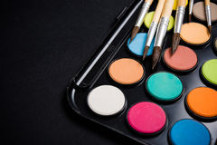 New watercolor paint set and brushes on artist's work desk. Creative art tools isolated on black background closeup royalty free stock photo