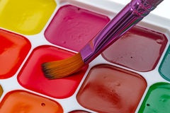 New watercolors and a brush. Water Colors pallet and brush closeup Royalty Free Stock Image