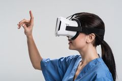 Pensive female doctor seizing virtual  table. New ways. Pretty nice female doctor  trying VR glasses and standing in profile while performing task in virtual Royalty Free Stock Photo