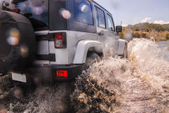 New 4wd fording river. Rear of silver modern unmarked 4wd offraod vehicle making large splashes crossing a stream Royalty Free Stock Photo