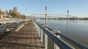 New Westminster Pier Park Boardwalk. The Fraser River flows under three bridges at dawn past a waterfront park and boardwalk in New Westminster, British Columbia stock footage