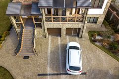 New white car parked in paved driveway with green lawn, decorative bushes and brick fence of big two story house with wide. Staircase and decorative porch royalty free stock images