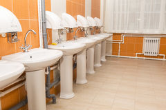 New white ceramic sinks and hand dryers. On the red tiled wall stock photos