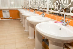 New white ceramic sinks and hand dryers. On the red tiled wall royalty free stock photo