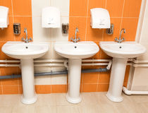 New white ceramic sinks and hand dryers. On the red tiled wall stock image