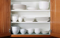 New White Dishes And Bowls In Kitchen Cabinet Stock Image