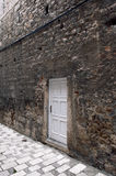 New white door on old ruined wall. New white door on old dirty wall in narrow paved street Royalty Free Stock Image