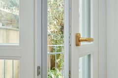 New, white double glazed open window with golden handle. In renovated apartment interior stock photography