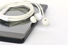 New white earphone and black smart phone Royalty Free Stock Photos