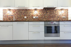 New white kitchen with stainless appliances, colorful  mosaic wall Royalty Free Stock Photos