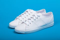 New white sneakers on blue background Stock Photos