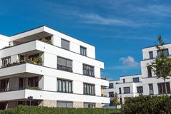 New white townhouses in front of a blue sky. Seen in Berlin, Germany Stock Photo