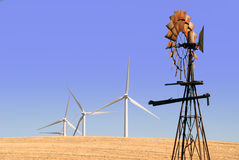 New Windmills for Old. Power generating windmills contrasted by rusted ranch windmill on wheat covered hills, Rio Vista California Royalty Free Stock Photo