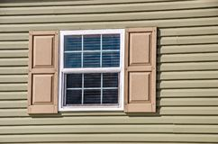 New Window On A New Home. Vinyl window and siding on a new manufactured home with shutters royalty free stock photo