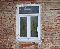 New window in the old house. New modern window in the old brick house royalty free stock images