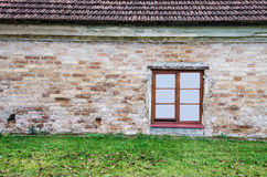 New window on old wall with lawn and roof Royalty Free Stock Image