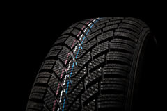 New winter tire isolated on black background Stock Image