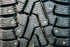 New winter tire with steel thorns, black rubber texture of car wheel Stock Images