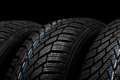 New winter tires isolated on black background Stock Photo