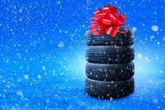 Free New Winter Tires Pile As A Gift. Tyres Pile With A Big Red Bow, As A Present Or Bonus For Buying A Car. Banner With Copy Space Royalty Free Stock Photo - 160136995
