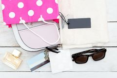 New women`s T-shirt and pink shopping bag. Flat lay Royalty Free Stock Photography