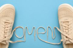 Women sneakers with laces in omen text. New women sneakers with laces in omen text. Flat lay on blue background royalty free stock photography