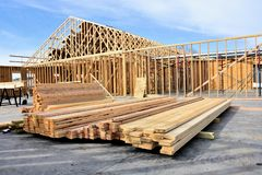 New wood frame home under construction. New wood frame home under construction with building materials in foreground royalty free stock photos