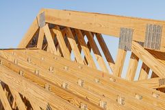 New wood pine trusses with metal joist hangers attached. Closeup of a bandeded stack of new wooden building trusses with joist hangers attached Stock Images