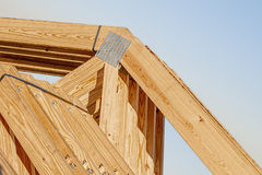 New wood pine trusses with metal joist hangers attached. Closeup of a bandeded stack of new wooden building trusses with joist hangers attached Stock Photography