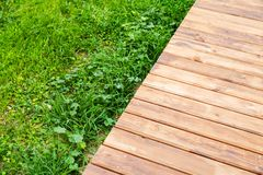 New wooden boardwalk over lawn in park stock images