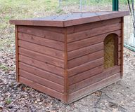 A new wooden dog house stands in a forest on sandy soil. A new wooden doghouse of modern components stands in a forest on sandy soil royalty free stock image