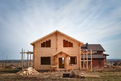 New wooden house built from logs, unfinished ecological wooden building on blue sky background stock photography