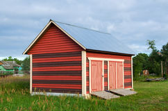 New wooden shed in the russian village. With painted walls and metal roof Stock Photography