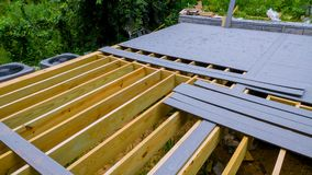 A new wooden, timber deck being constructed. it is partially completed can be seen on the decking. A new wooden, timber deck being constructed completed can be royalty free stock photos