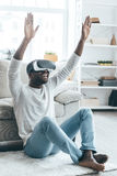 New word of virtual reality!. Handsome young African man in VR headset gesturing and smiling while sitting on the carpet at home Stock Images