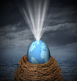 New World. Business concept with a glowing global egg symbol resting on a nest surrounded by the risk of severe weather as an icon of hope and development of Royalty Free Stock Images