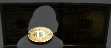 New world currency. Gold coin of Bitcoin and silhouette of Benja. Min Franklin Franklin on the one hundred dollars USA. Bitcoin concept. Money concept Stock Photo