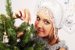 New year. The Snow Maiden dresses up a fur-tree by New year Stock Photo